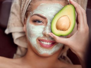 portrait of a young woman applying natural avocado mask on her